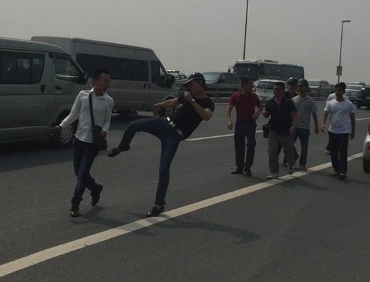 Nhà báo Quang Thế (áo trắng) bị nhóm thanh niên hành hung khi tác nghiệp trên cầu Nhật Tân sáng 23-9Ảnh: Minh Chiến