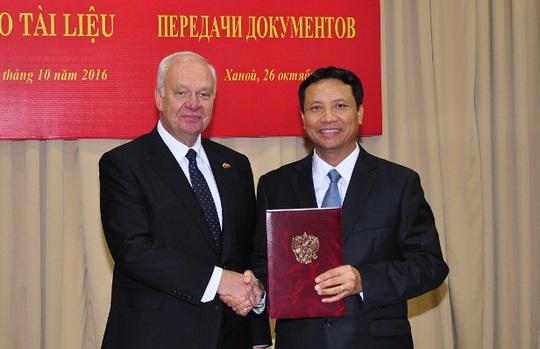 Đại sứ Nga tại Việt Nam K.V.Vnukov (trái) chuyển giao các tài liệu cho đại diện Ban quản lý Lăng Chủ tịch Hồ Chí Minh