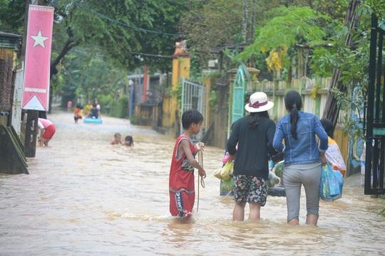 Người dân hối hả chạy lũ trong khi trẻ em vui đùa trong nước lũ khá nguy hiểm