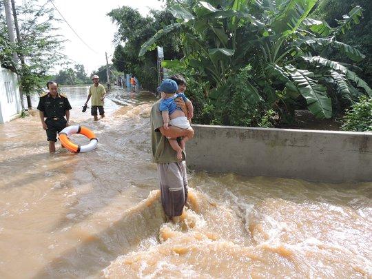 Người dân khẩn trương sơ tán ra khỏi nước lũ. Ảnh: Duy Anh