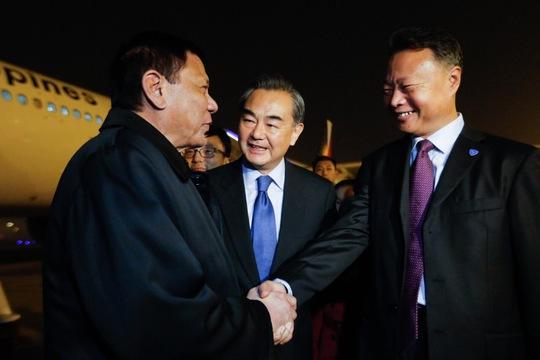 Ngoại trưởng Trung Quốc Vương Nghị (giữa) và đại sứ Trung Quốc tại Philipppines Triệu Kiếm Hoa đón Tổng thống Philippines Rodrigo Duterte (trái) ở sân bay Bắc Kinh. Ảnh: Reuters