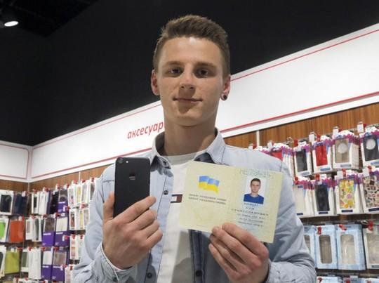 Olexander Turin với trang hộ chiếu đã đổi tên thành iPhone Sim và chiếc điện thoại iPhone 7 được tặng miễn phí. Ảnh: AP