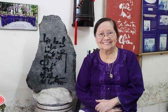 """Nhà thơ Tôn Nữ Hỷ Khương bên phiến đá có khắc 2 câu thơ hay trong bài """"Còn gặp nhau"""" Ảnh: MINH LÊ"""