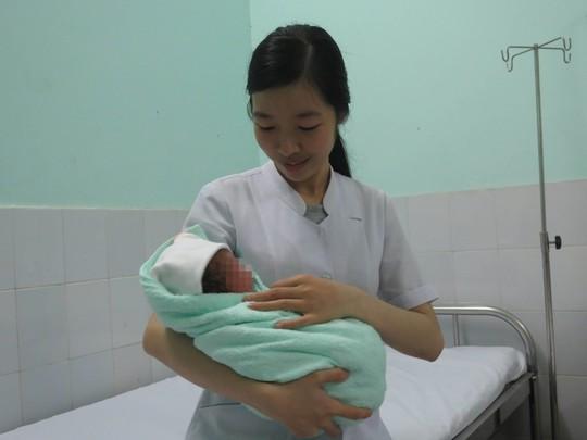 Bé trai mới sinh trong vòng tay một nữ hộ sinh của Bệnh viện Quận Gò Vấp