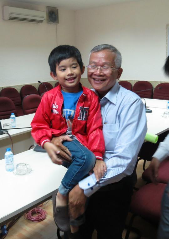 Cậu bé vui đùa trong vòng tay BS Trần Văn Sơn, người mà cậu đã cầu cứu khi mới nhập viện