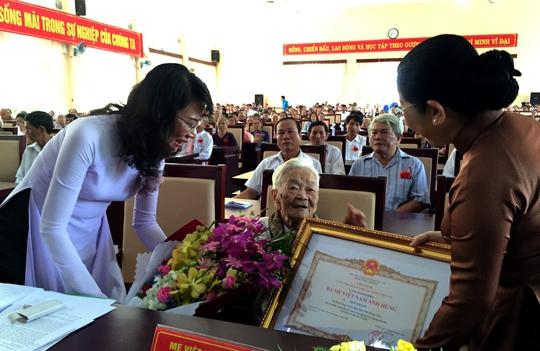 Bà Võ Thị Dung – Phó Bí thư Thành ủy (phải) và bà Nguyễn Thị Thu – Phó Chủ tịch UBND TP HCM cùng trao danh hiệu và hoa đến mẹ Trần Thị Sơn