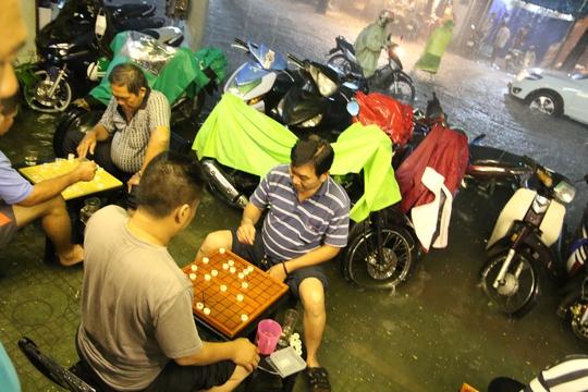 Người dân trên đường Trần Nhân Tôn, quận 10 đánh cờ trong khi nước ngập đến chân. - Ảnh: LÊ PHONG
