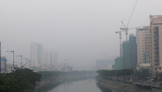 Đứng trên cầu Nguyễn Văn Cừ (quận 5) nhìn về hướng quận 1, các toà nhà bị che khuất lớp sương trắng đục.