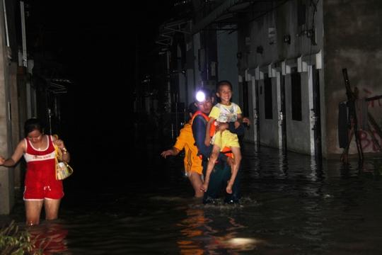 Một cháu bé được di tản khỏi điểm ngập tại phường Tân Hiệp, Tân Uyên. Vùng này tối 26-9 chỗ ngập sâu nhất đến 1,5 m