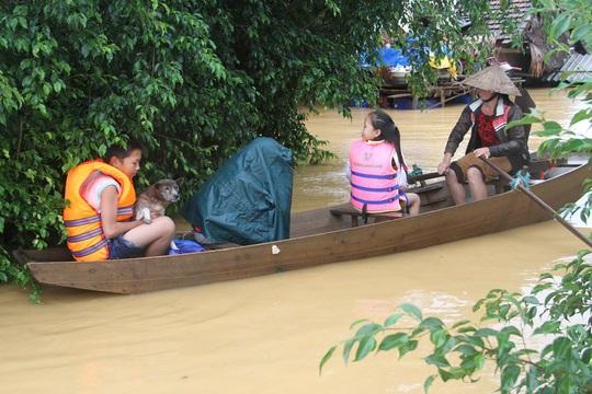 Người dân dùng thuyền di chuyển trong nước lũ.