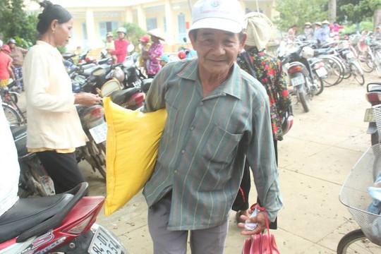 Người dân vui vẻ nhận tiền và gạo từ gia đình chị Đ. Ảnh: Lê Khánh