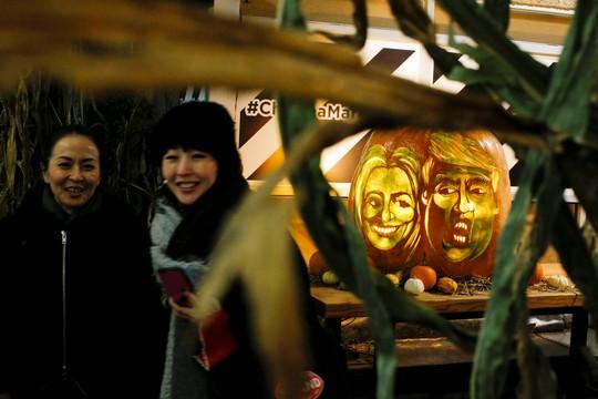 Quả bí ngô hình khuôn mặt của bà Clinton và ông Trump tại chợ Chelsea ở New York ngày 28-10 Ảnh: REUTERS