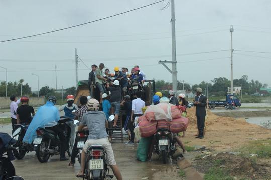 """Người dân vùng lũ """"xếp hàng"""" chờ lên xe tải """"tăng bo"""" qua những đoạn đường ngập nước"""