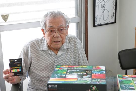 Ông Takayasu Watanabe và sản phẩm phấn viết của gia đình Ảnh: REUTERS