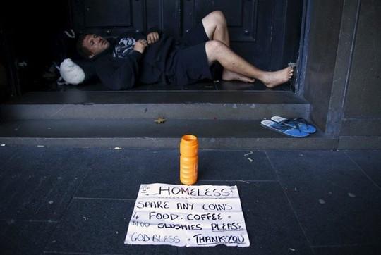 Một người đàn ông xin tiền ở lối thoát hiểm của tòa nhà ở Sydney (Australia). Ảnh: Thomson/Reuters.