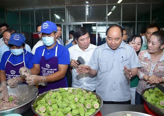 Thủ tướng thăm cơ sở chế biến suất ăn công nghiệp Tú Anh. Ảnh: VGP/Quang Hiếu