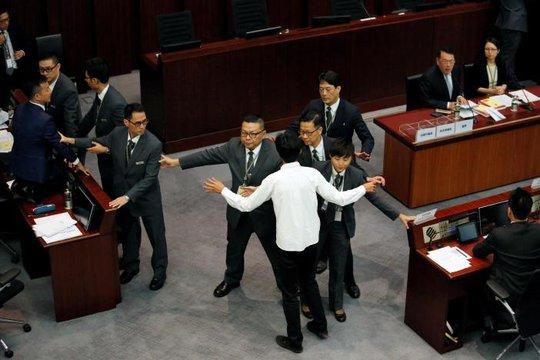 Nghị sĩ Eddie Chu (áo trắng) và Raymond Chan bị nhân viên an ninh chặn lại khi cố ngăn cản phiên bầu chủ tịch Legco. Ảnh: Reuters