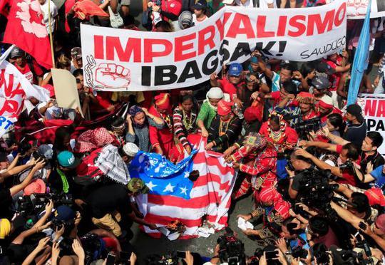 Cờ Mỹ bị đốt trong một cuộc biểu tình ở Manila hôm 21-10. Hàng trăm người cách tả tham gia biểu tình để kêu gọi chấm dứt các thỏa thuận quân sự với Mỹ. Ảnh: Reuters