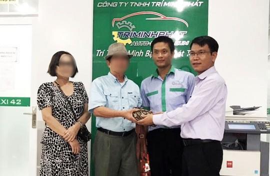 Đại diện hãng xe Taxi 42 trả lại tài sản bỏ quên cho ông Được và bà Hà (bìa trái).