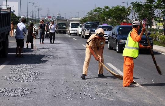 Lực lượng CSGT phụ công nhân vệ sinh dọn dẹp đá dăm rơi vãi trên đường Phạm Văn Đồng.