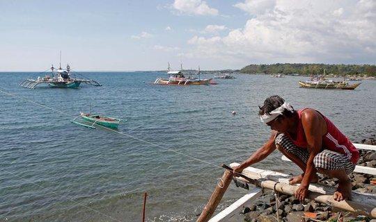 Ngư dân Philippines sửa lại thuyền dùng để đánh bắt ở bãi cạn Scarborough. Ảnh: REUTERS