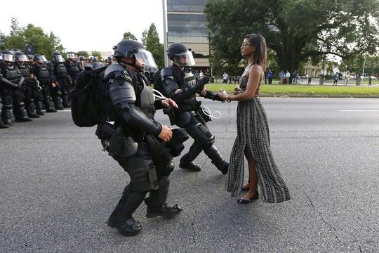 Một phụ nữ tên Ieshia Evans đối đầu với lực lượng thực thi pháp luật trong cuộc biểu tình phản đối vụ cảnh sát bắn chết Alton Sterling ở TP Baton Rouge, bang Louisiana - Mỹ hôm 9-7. Ảnh: Reuters.