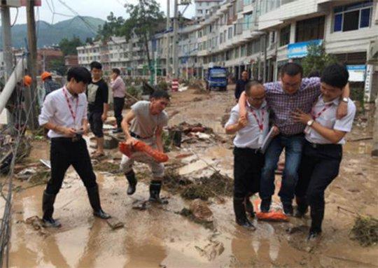 Bức ảnh ghi lại cảnh ông Bao được 2 nhân viên công ty bảo hiểm khiêng qua vũng nước. Ảnh: TÂN HOA XÃ
