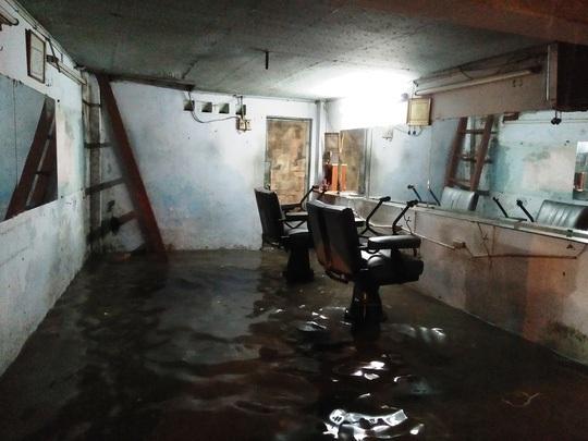 Một tiệm cắt tóc trên đường Nguyễn Xí, quận Bình Thạnh thu dọn đồ đạc đóng cửa sớm vì ngập