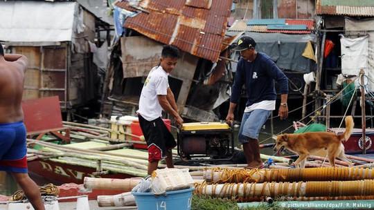Ngư dân thu dọn sau bão Sarika Ảnh: DPA