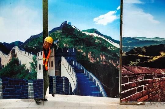 Một công nhân nhìn qua hàng rào tại công trình xây dựng nhà ga Bát Đạt Lĩnh. Ảnh: REUTERS