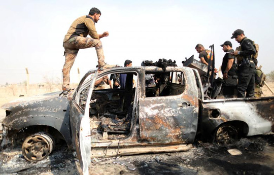 Binh sĩ Iraq và chiếc xe của IS bị phá hủy gần Mosul. Ảnh: Reuters