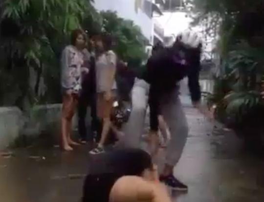 Nhí Tinô (mặc áo đen) đang đạp vào đầu và đánh một nữ sinh khác ở huyện Nhà Bè (TP HCM).