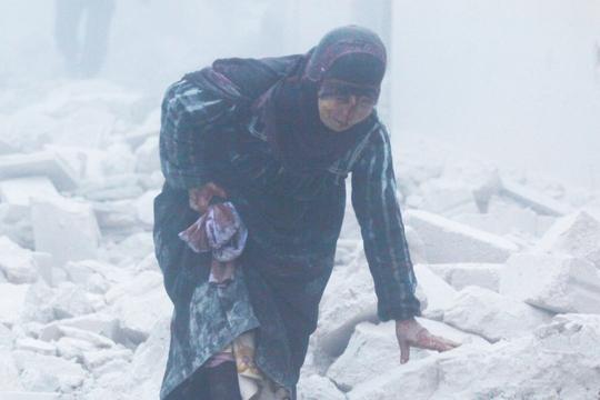 Một phụ nữ bị thương trong vụ không kích xuống khu vực do phe nổi dậy kiểm soát ở TP Aleppo hôm 7-12 Ảnh: Reuters