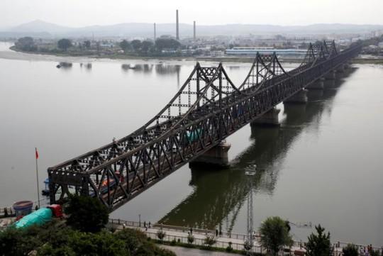 Xe tải chở hàng băng qua chiếc cầu nối từ tỉnh Liêu Ninh - Trung Quốc đến TP Sinuiju - Triều Tiên. Ảnh: Reuters