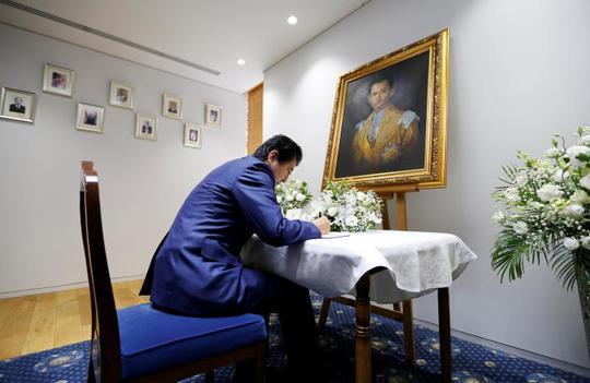 Thủ tướng Nhật Bản Shinzo Abe viết vào sổ chia buồn tại đại sứ quán Thái Lan ở Tokyo. Ảnh: Reuters