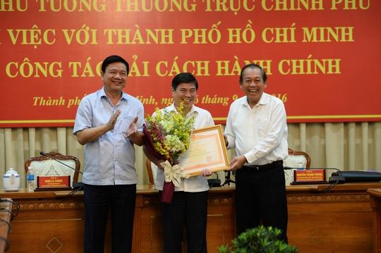 Phó Thủ tướng Thường trực Trương Hòa Bình (bìa phải) trao bằng khen của Thủ tướng Chính phủ cho UBND TP HCM về thành tích cải cách hành chínhẢnh: TRƯỜNG HOÀNG
