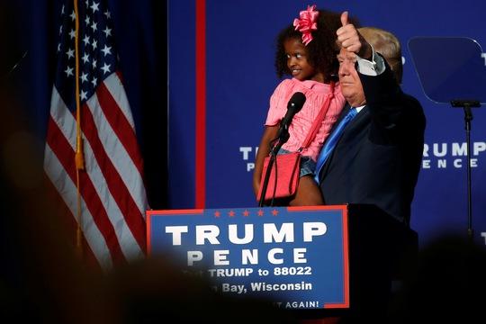 Ông Donald Trump bế 1 đứa trẻ trên khán đài ở Green Bay, bang Wisconsin đêm 17-10 Ảnh: REUTERS