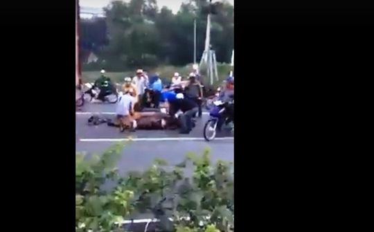 Người đi xe máy phải chạy ra làn xe tải để né nhóm người xẻ thịt trâu