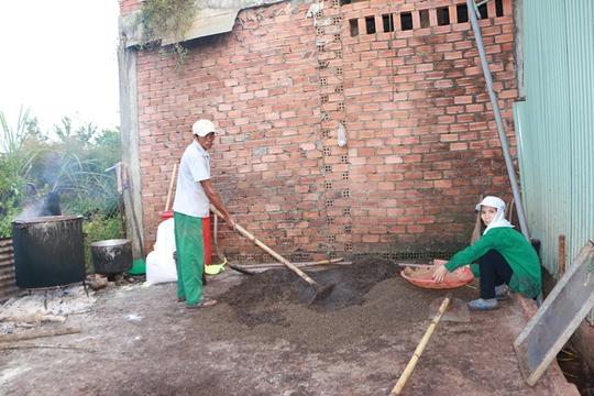 Ông Lệ và bà Cúc đang trộn hợp chất vừa nấu xong vào đống hạt tiêu lép để trộn đều cho kết dính vào hạt tiêu.