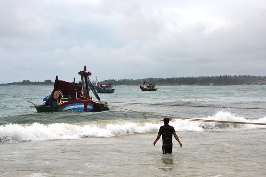 Chiếc tàu cá bị sóng lớn đánh chìm đang được kéo vào bờ. Ảnh: Tử Trực