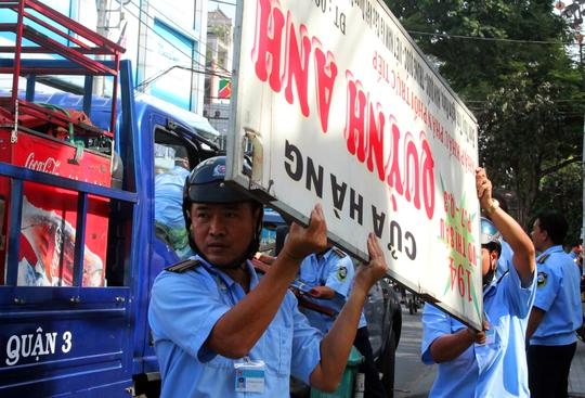 Lực lượng chức năng tiến hành tháo dỡ các biển hiệu lấn ra ngoài vỉa hè.