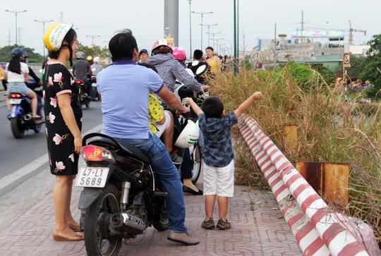 Một cậu bé gọi bố mẹ dừng xe lại, tỏ ra phấn khích khi được ngắm các cánh diều đủ sắc màu bay phấp phới trên bầu trời.