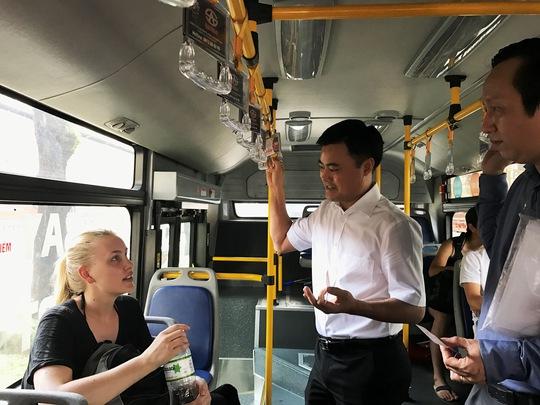 Ông Bùi Xuân Cương trò chuyện vui vẻ với nữ du khách trên xe buýt