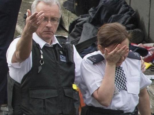 Hai cảnh sát Anh tại hiện trường vụ lao xe ở London hôm 22-3. Một trong hai người không có súng. Ảnh: AP