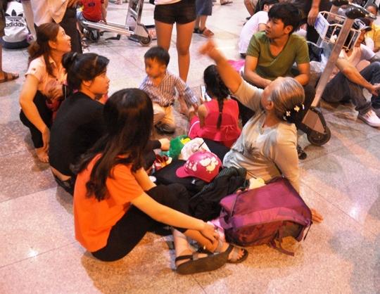 """Trong khi đó, do chờ đợi lâu vào đêm khuya khiến nhiều nhóm người tỏ ra mệt mỏi. Có gia đình còn mang theo đồ ăn, ngồi bệt xuống nền nhà ga ăn uống trong lúc chờ đợi. """"Mấy năm rồi ông bà nội mới từ Mỹ về nước nên gia đình tôi chạy xe từ Tiền Giang lên TP HCM để đón. Tuy nhiên, tôi không nghĩ đến cảnh tượng chen lấn, đông người như thế này"""" – chị Nguyễn Thùy Trang (32 tuổi) nói."""