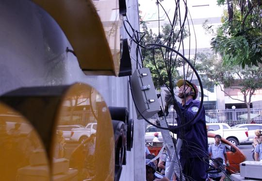 Do trên tường gắn nhiều thiết bị điện, nhân viên điện lực được cử đến để xử lý, ngắt nguồn điện trước khi tháo dỡ.