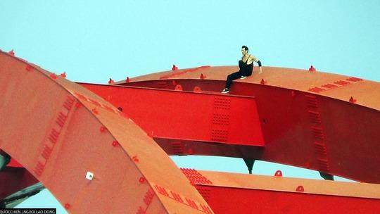Nam thanh niên người nước ngoài leo lên nóc, chạy qua các thanh ngang của cầu Bình Lợi.