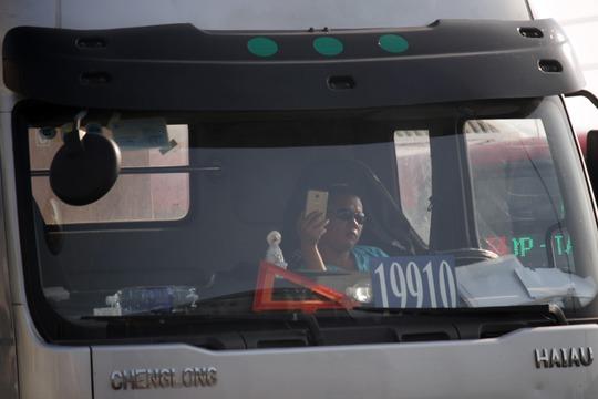Hậu quả là làn xe ô tô cũng kẹt cứng. Trong ảnh là một tài xế xe tải bất lực ngồi nhìn và dùng điện thoại phát trực tiếp cảnh kẹt xe.