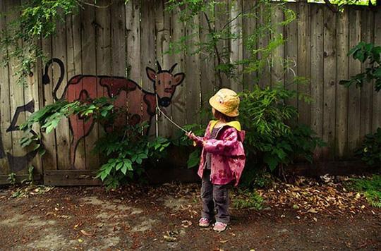"""Không chỉ sáng tạo ra các tác phẩm thú vị, con người còn có thể tương tác với nó nữa. Trong ảnh là một bé gái đang cố """"dắt"""" chú bò sữa ra ngoài đám lá cây. Chắc có lẽ vì… giống thật quá nên cô bé nhà ta lầm chăng?"""