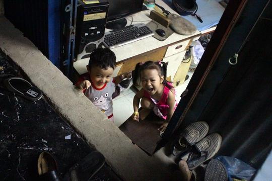 Hai đứa trẻ chơi đùa trước cửa nhà, trong không gian bức bối